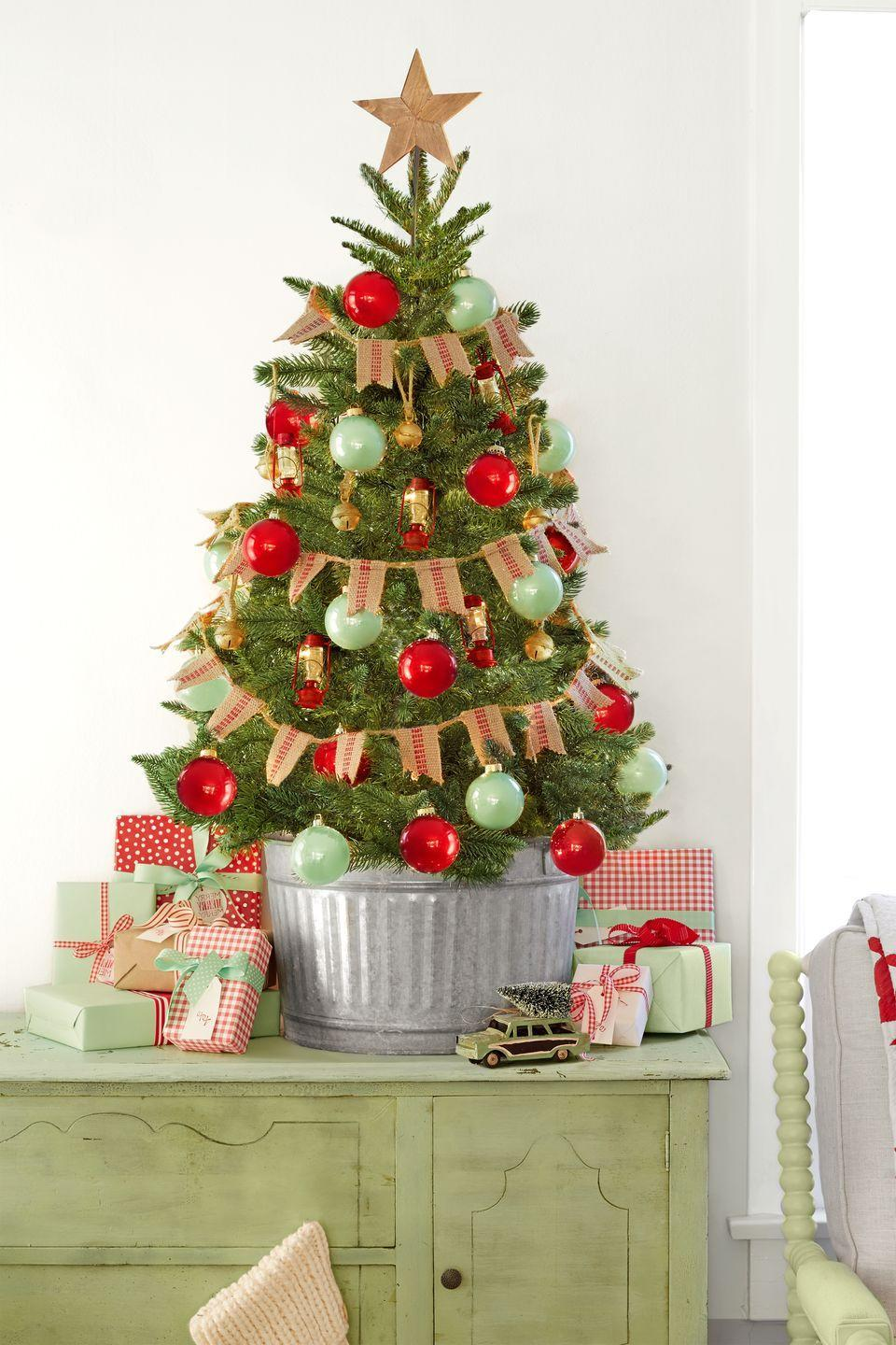 "<p>This mini Christmas tree brings major country charm thanks to its burlap banner, galvanized bucket, and lantern ornaments.</p><p><a class=""link rapid-noclick-resp"" href=""https://go.redirectingat.com?id=74968X1596630&url=https%3A%2F%2Fwww.etsy.com%2Flisting%2F600028460%2Fblank-mini-burlap-banner-diy-burlap&sref=https%3A%2F%2Fwww.countryliving.com%2Fhome-design%2Fdecorating-ideas%2Fg316%2Fdecorate-mini-christmas-trees%2F"" rel=""nofollow noopener"" target=""_blank"" data-ylk=""slk:SHOP MINIATURE BURLAP BUNTING"">SHOP MINIATURE BURLAP BUNTING</a></p>"