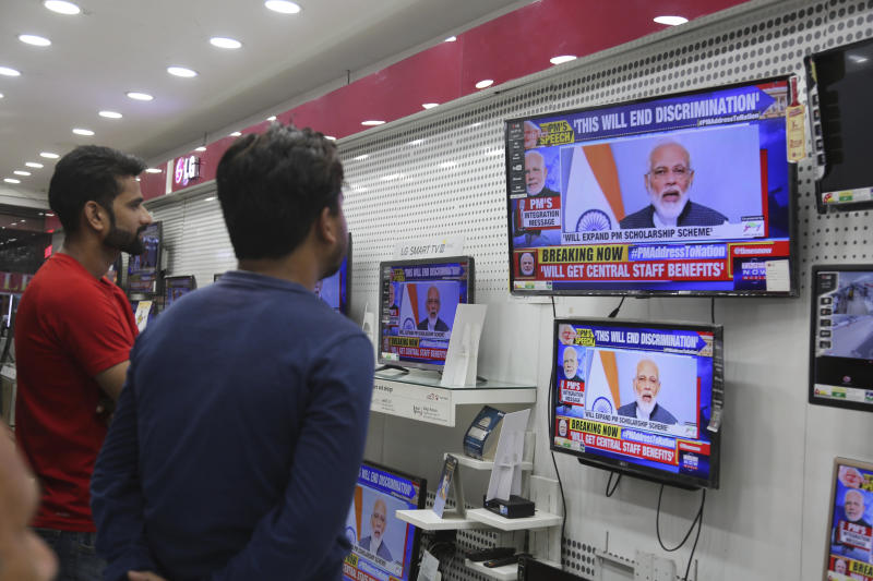 "FILE - In this Thursday, Aug. 8, 2019, file photo, Indians watch Prime Minister Narendra Modi address the nation in a televised speech, in an electronics store in Jammu, India. Modi has promised early elections in the Indian-controlled portion of Kashmir days after stripping it of statehood and turning it into a federally administered territory. In an address to the nation, Modi said the change in Kashmir's set-up will help free the disputed region of ""terrorism and separatism"" and put it on a path of development. (AP Photo/Channi Anand, File)"