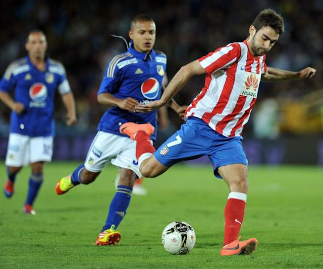 "Adrian Lopez (R) of Spanish Atletico de Madrid prepares to kick the ball during the friendly football match against Colombia's Millonariosheld at the Nemesio Camacho ""El Campin"" stadium in Bogota, Colombia, on May 16, 2012. AFP PHOTO/Guillermo LegariaGUILLERMO LEGARIA/AFP/GettyImages"