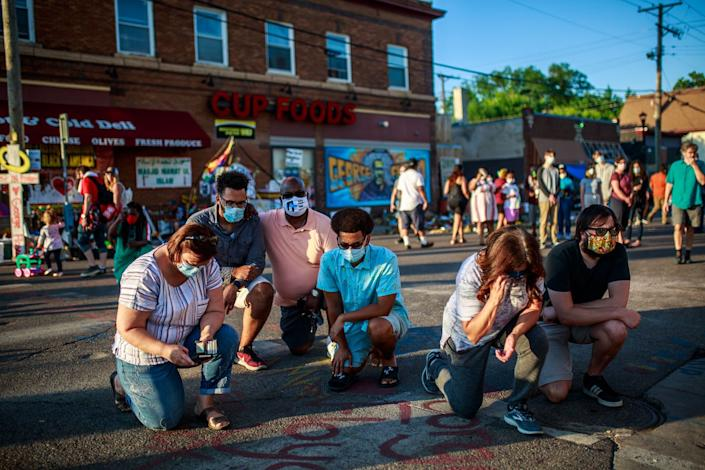 """<span class=""""caption"""">People kneel and pray outside Cup Foods in Minneapolis.</span> <span class=""""attribution""""><a class=""""link rapid-noclick-resp"""" href=""""https://www.gettyimages.com/detail/news-photo/people-kneel-and-pray-outside-the-cup-foods-market-in-front-news-photo/1221540533?adppopup=true"""" rel=""""nofollow noopener"""" target=""""_blank"""" data-ylk=""""slk:Kerem Yucel/AFP via Getty Images"""">Kerem Yucel/AFP via Getty Images</a></span>"""