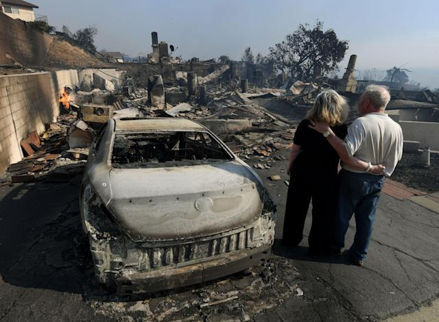 <p>Michael and Vonea McQuillam stand beside their house that was burnt to the ground during the Thomas wildfire in Ventura, Calif., on Dec. 5, 2017. (Photo: Mark Ralston/AFP/Getty Images) </p>