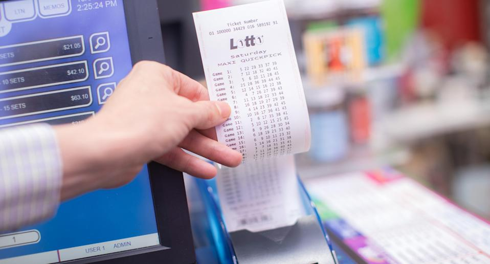 Man holding ticket for Saturday's Lotto $30 Million Megadraw