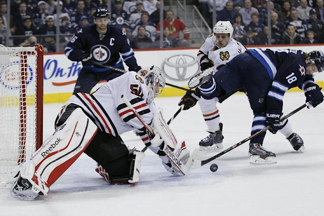 Chicago Blackhawks goaltender Corey Crawford (50) stops Winnipeg Jets' Bryan Little (18) backhander as Hawks' Niklas Hjalmarsson, second from right, and Jets' Andrew Ladd (16) look for the rebound during the second period of an NHL hockey game in Winnipeg, Manitoba on Thursday, Nov. 21, 2013. (AP Photo/The Canadian Press, John Woods)