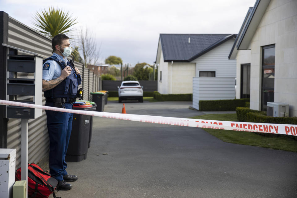 A police officer stands in the driveway of a house where three children were found dead in the South Island town of Timaru, New Zealand, Friday, Sept. 17, 2021. Three young children who had just moved to New Zealand from South Africa have died in what police are investigating as homicide. (George Heard/New Zealand Herald via AP)