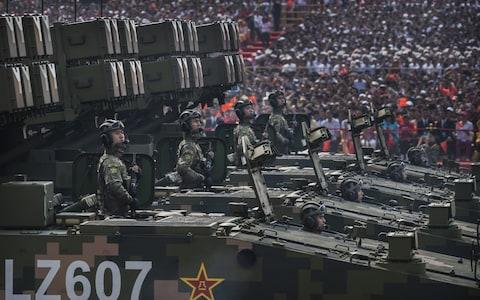 Chinese soldiers sit atop mobile rocket launchers - Credit: Getty