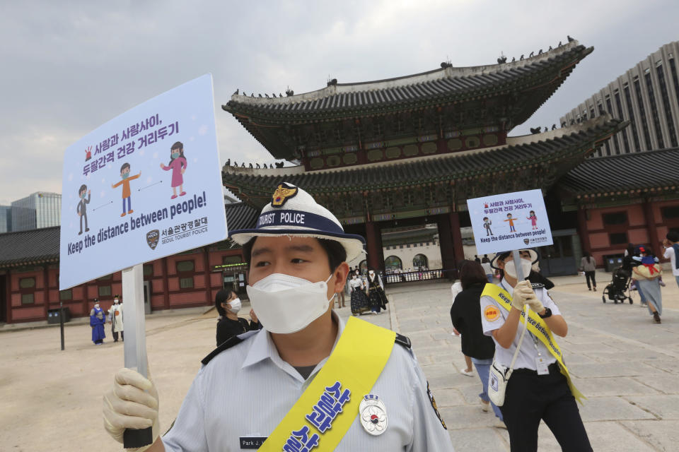 South Korean tourist police officers wearing face masks hold up social distancing signs at the Gyeongbok Palace in Seoul, South Korea, Wednesday, Sept. 30, 2020. Officials have called for citizen vigilance ahead of the Chuseok harvest festival that began Wednesday and continues through the weekend. (AP Photo/Ahn Young-joon)