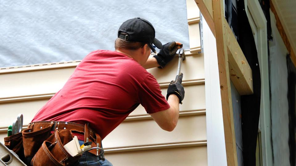 Young homeowner installs siding to his home.