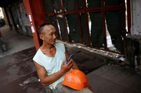 FILE PHOTO: A worker rests against a wall in an area filled with small blue-collar workshops in Kok Tsui in Hong Kong