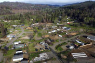 The town of Otis, Ore., is seen in this aerial photo on Thursday, May. 13, 2020. The small Oregon coast town is still recovering from the devastating fire that destroyed 293 homes. Experts say the 2020 wildfire season in Oregon was a taste of what lies ahead as climate change makes blazes more likely and more destructive even in wetter, cooler climates like the Pacific Northwest. (AP Photo/Craig Mitchelldyer)