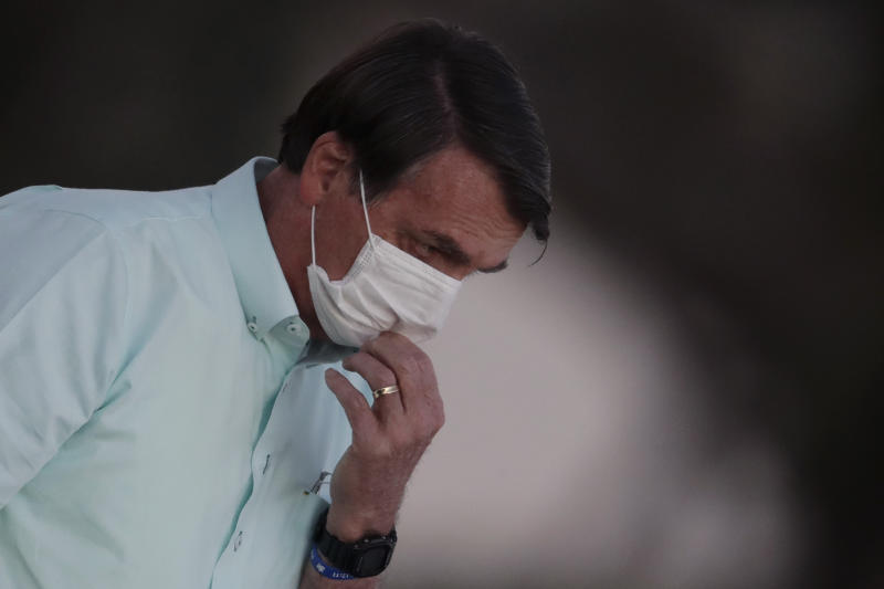 Brazil's President Jair Bolsonaro, who is infected with COVID-19, adjusts his protective face mask while attending a Brazilian flag retreat ceremony outside his official residence the Alvorada Palace, in Brasilia, Brazil, Wednesday, July 22, 2020. Bolsonaro has tested positive for the new coronavirus for the third time, following his July 7 an