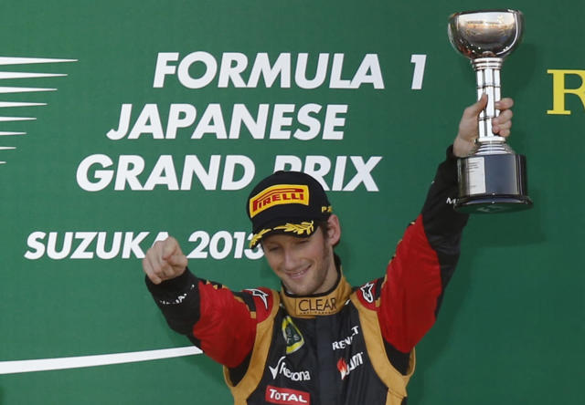 Third-placed Lotus Formula One driver Romain Grosjean of France raises his trophy on the podium after the Japanese F1 Grand Prix at the Suzuka circuit October 13, 2013. REUTERS/Toru Hanai (JAPAN - Tags: SPORT MOTORSPORT F1)