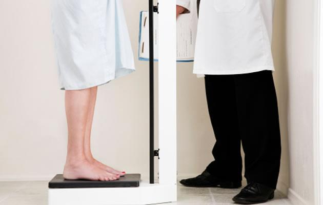 A doctor weighing a patient. (Getty Images)
