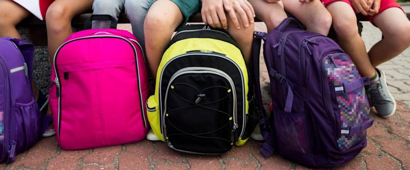 primary education, learning, childhood and people concept - close up of elementary school students with backpacks and notebooks sitting on bench outdoors
