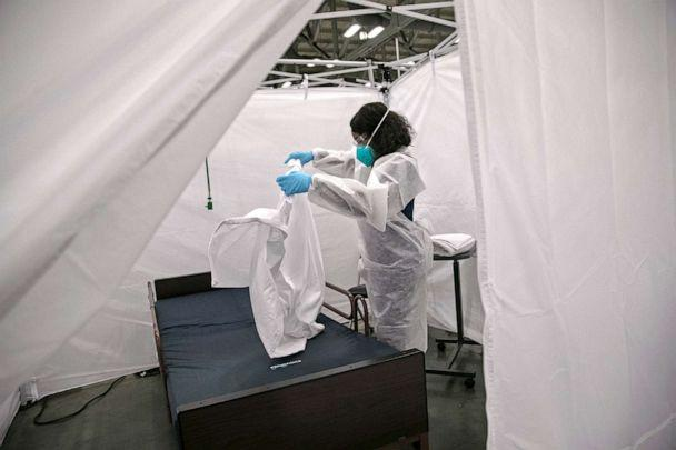 PHOTO: A nurse makes a bed in a Covid-19 isolation bay at the Austin Convention Center on Aug. 7, 2020 in Austin, Texas. The cavernous facility was prepared for use as a field hospital for Covid-19 patients, if Austin hospitals were to become overwhelmed. (John Moore/Getty Images, FILE)