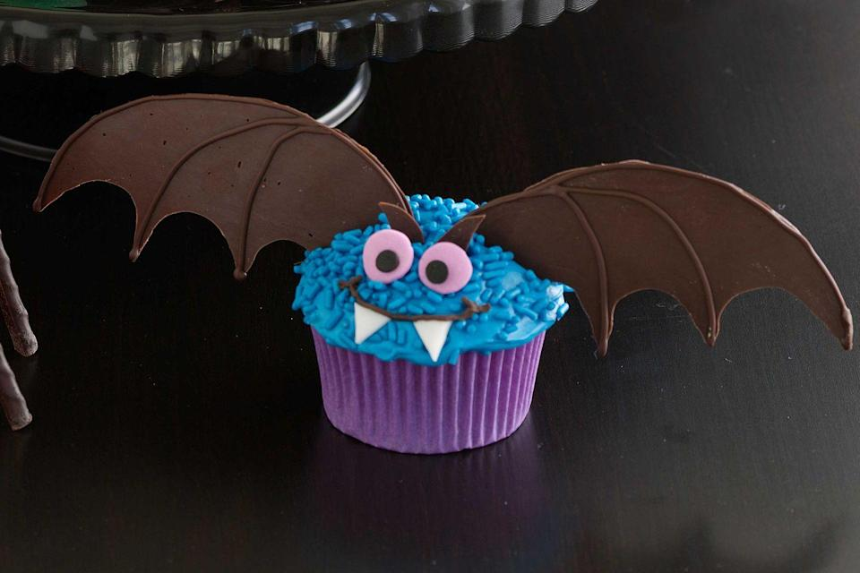 """<p>Plain cupcakes take flight once decorated with blue frosting and sprinkles, dark chocolate wings, and sugar-spun eyes and fangs.</p><p><a href=""""https://www.womansday.com/food-recipes/food-drinks/recipes/a10836/bat-cupcake-122195/"""" rel=""""nofollow noopener"""" target=""""_blank"""" data-ylk=""""slk:Get the Bat Cupcake recipe."""" class=""""link rapid-noclick-resp""""><em>Get the Bat Cupcake recipe.</em></a></p>"""