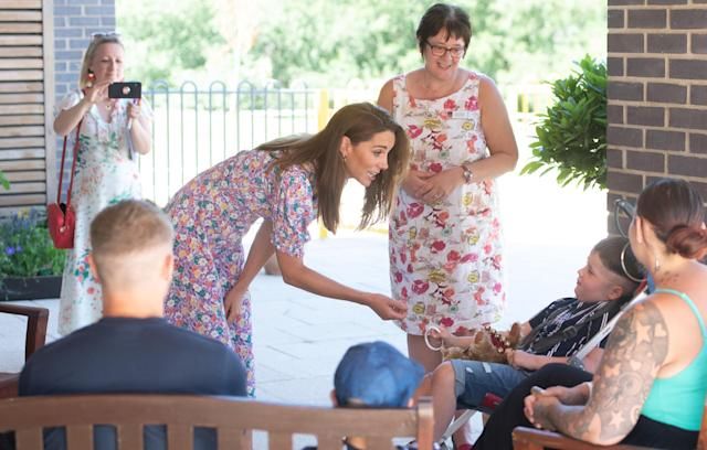 Kate meeting Sonny Saunders, who gives her a bracelet, and his family, including mother Kelly (right, back to camera) and father Jordan (left, back to camera). (PA Images)
