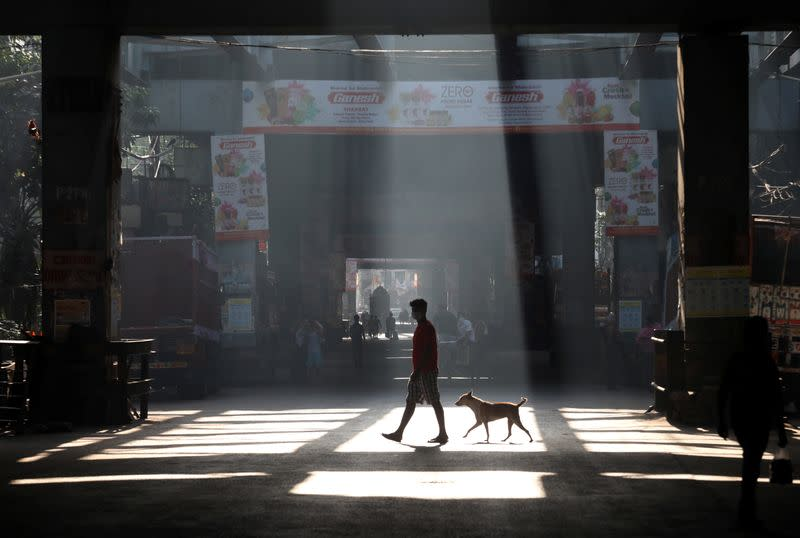 A man and a stray dog cross a road during a 21-day nationwide lockdown to limit the spreading of coronavirus disease (COVID-19), in Kolkata