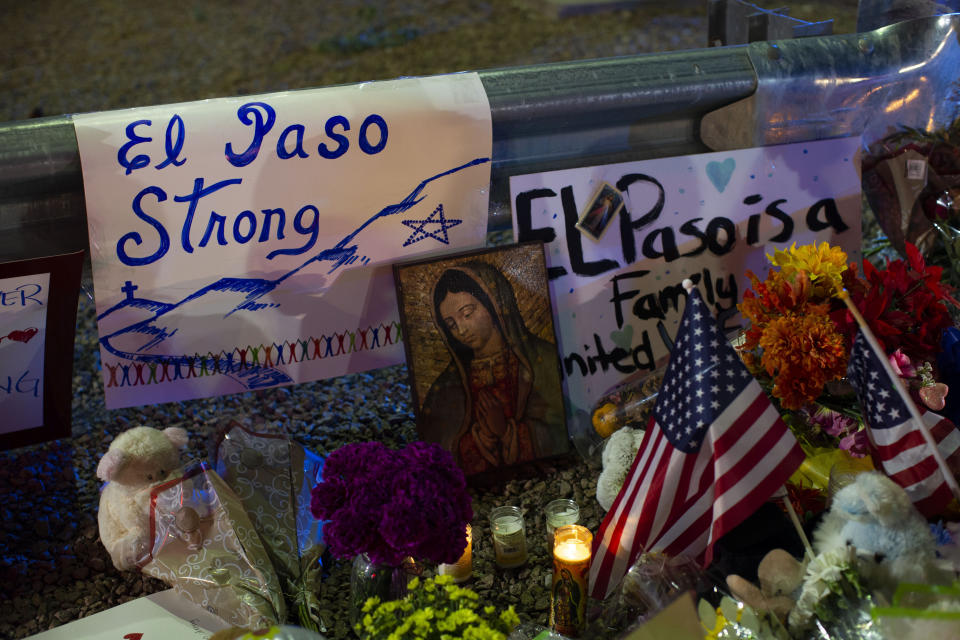 A Virgin Mary painting, flags and flowers adorn a makeshift memorial for the victims of Saturday's mass shooting at a shopping complex in El Paso, Texas, Sunday, Aug. 4, 2019. (AP Photo/Andres Leighton)
