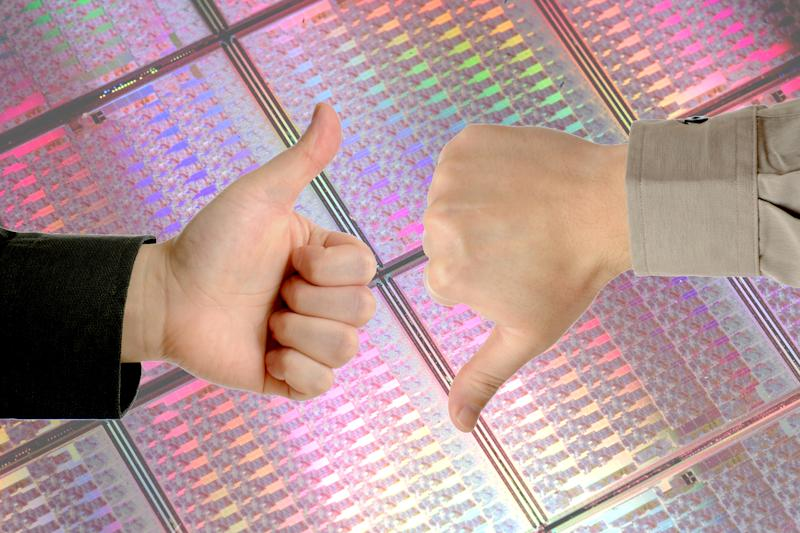 Two hands in business-style sleeves giving thumbs-up and thumbs-down signs against a backdrop of uncut silicon wafers.