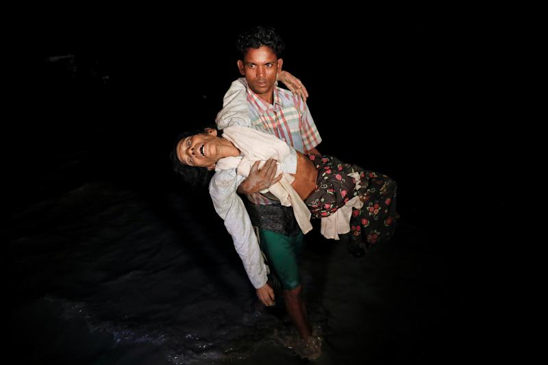 Nobi Hossain wades through the water carrying his elderly relative, Sona Banu, as hundreds of Rohingya refugees arrive by wooden boats from Myanmar to the shore near Cox's Bazar in Bangladesh, on Sept. 27. (Damir Sagolj/Reuters)