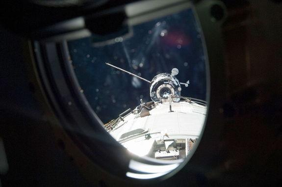 The Progress M-19M (51P) Russian cargo craft is seen through a window arriving at the International Space Station in April 2013. It departed on June 11 packed with trash, including the station's first treadmill, destined to be destroyed during