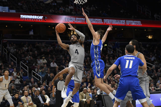 Georgetown guard Jagan Mosely (4) goes to the basket next to Creighton forward Christian Bishop, right center and guard Marcus Zegarowski (11) during the second half of an NCAA college basketball game, Wednesday, Jan. 15, 2020, in Washington. Georgetown won 83-80. (AP Photo/Nick Wass)