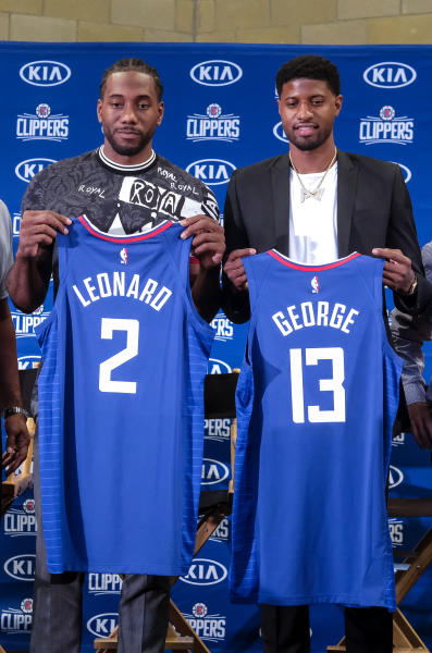 Kawhi Leonard, left, and Paul George pose with their new team jerseys during a press conference in Los Angeles, Wednesday, July 24, 2019. Nearly three weeks after the native Southern California superstars shook up the NBA by teaming up with the Los Angeles Clippers, the dynamic duo makes its first public appearance. (AP Photo/Ringo H.W. Chiu)