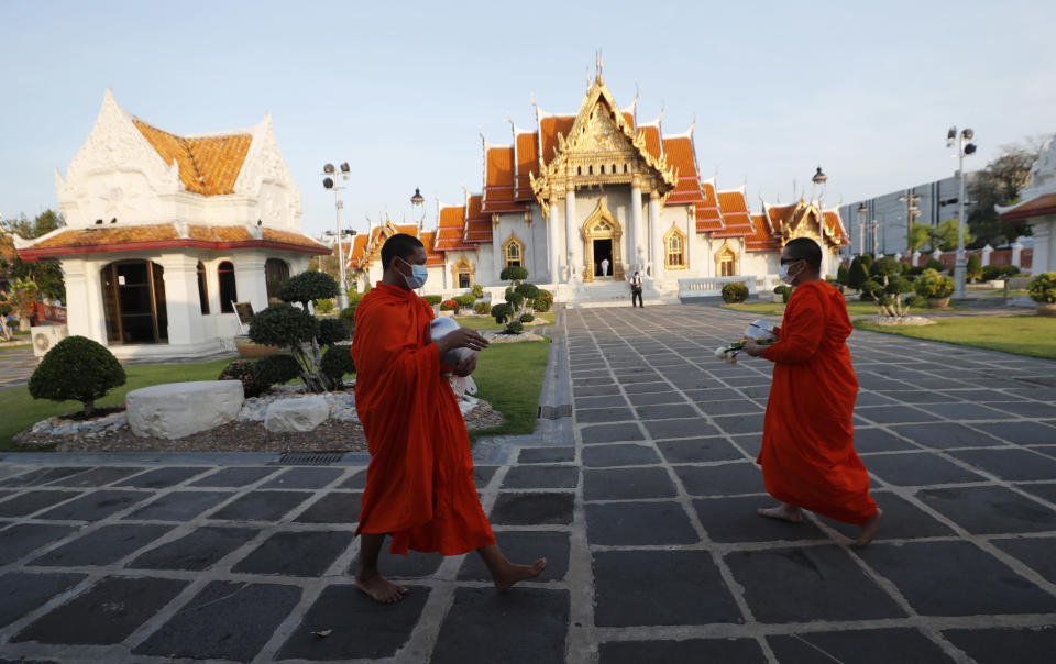 Buddhist monks wear face masks to protect themselves from the coronavirus during a morning alms offerings at Marble Temple in Bangkok, Thailand Friday, April 16, 2021. (AP Photo/Sakchai Lalit)
