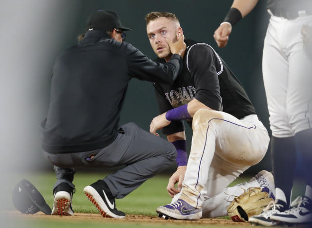 Rockies shortstop Trevor Story is attended to after being hit on the face by a grounder. (AP Photo/David Zalubowski)