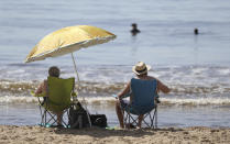 People sit by the beach on a sunny day, in Bournemouth, England, Wednesday, May 20, 2020. Lockdown restrictions due to the coronavirus outbreak have been relaxed allowing unlimited outdoor exercise and activities such as sunbathing. (Andrew Matthews/PA via AP)