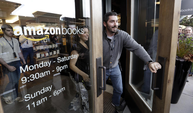 FILE - In this Tuesday, Nov. 3, 2015, file photo, employees smile as they unlock and open the door to the first customers at the opening day for Amazon Books, the first brick-and-mortar retail store for online retail giant Amazon. Although Amazon already dominates e-commerce, 90 percent of worldwide retail spending is still in brick-and-mortar stores, according to eMarketer. Amazon has the chance to change retail with automation and data-mining technologies borrowed from e-commerce. (AP Photo/Elaine Thompson, File)