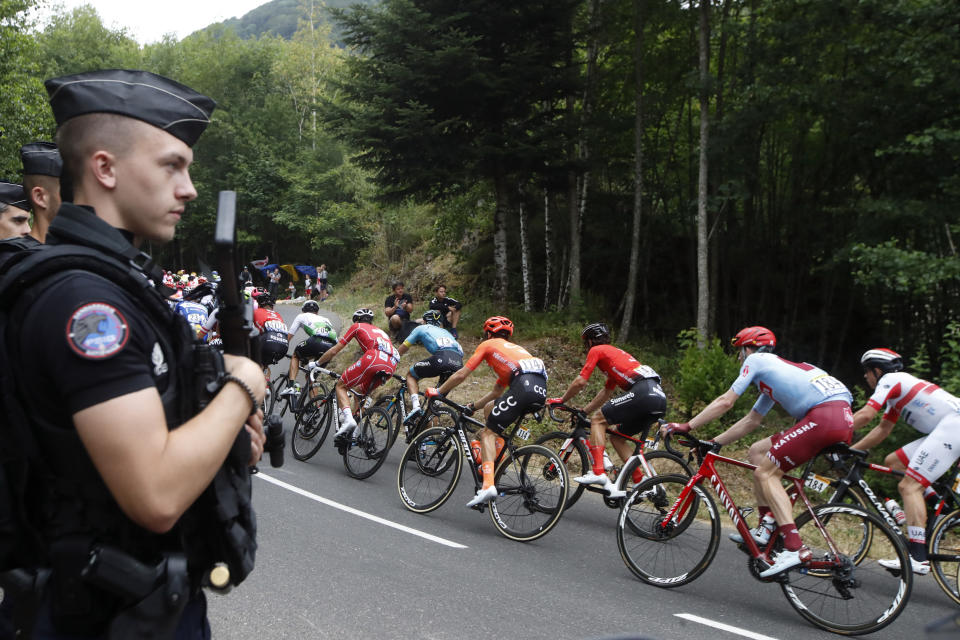 The pack rides past police officers during the sixth stage of the Tour de France cycling race over 160 kilometers (100 miles) with start in Mulhouse and finish in La Planche des Belles Filles, France, Thursday, July 11, 2019. (AP Photo/Christophe Ena)