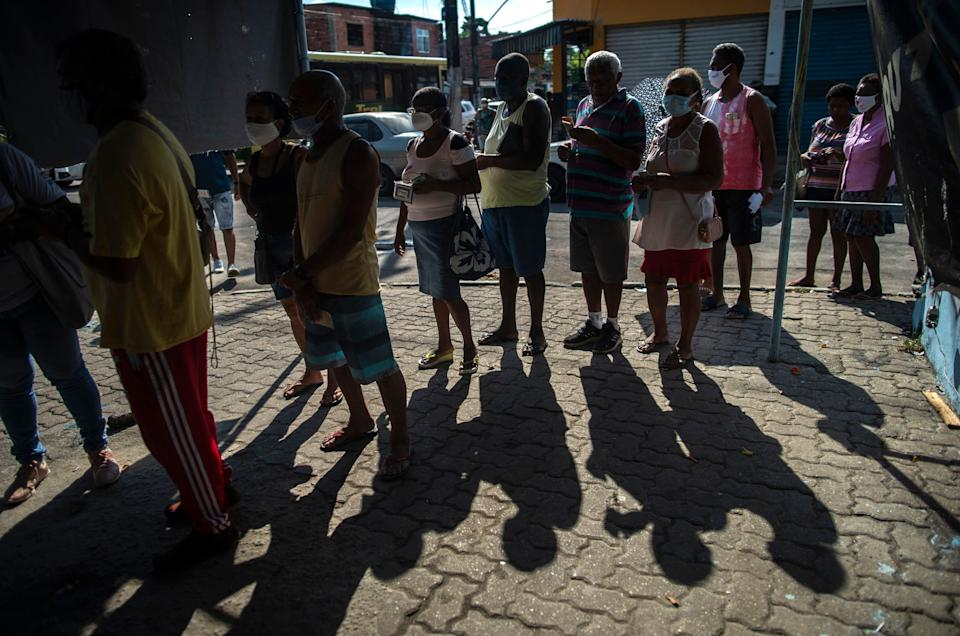People wearing face masks queue for their turn to receive a dose of the COVID-19 vaccine at a vaccination center on Cangulo square, Saracuruna neighbourhood, in Duque de Caxias, Rio de Janeiro state, Brazil, on March 30, 2021. (Photo by Mauro Pimentel / AFP) (Photo by MAURO PIMENTEL/AFP via Getty Images)