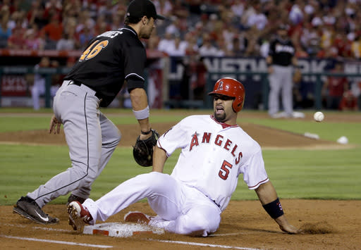 Los Angeles Angels' Albert Pujols, right, reacts after getting ht by a throw after sliding back to first as Miami Marlins first baseman Garrett Jones goes to the ball during the third inning of a baseball game in Anaheim, Calif., Tuesday, Aug. 26, 2014. (AP Photo/Chris Carlson)