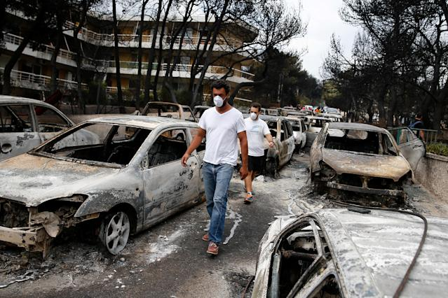 <p>Locals wearing masks walk among burnt cars following a wildfire at the village of Mati, near Athens, Greece, July 24, 2018. (Photo: Costas Baltas/Reuters) </p>