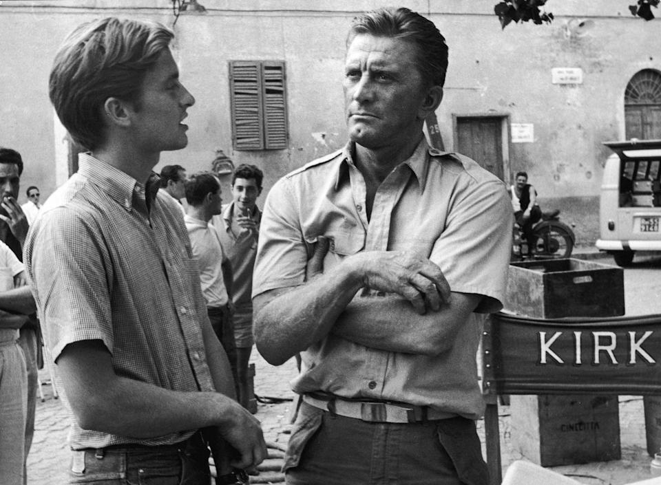 """<p>While on set for his film <em>Cast a Giant Shadow, </em>Kirk is joined by his son, Michael. The actor gave his son pointers for his first on-screen performance <a href=""""https://www.imdb.com/name/nm0000140/?ref_=fn_al_nm_1"""" rel=""""nofollow noopener"""" target=""""_blank"""" data-ylk=""""slk:in an uncredited role"""" class=""""link rapid-noclick-resp"""">in an uncredited role</a>. </p>"""