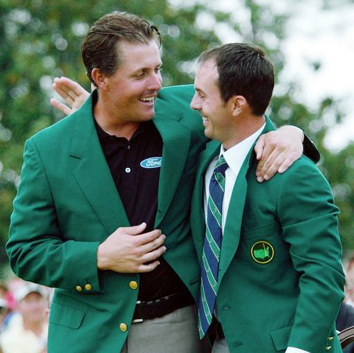FILE - In this April 11, 2004, file photo, Phil Mickelson hugs last year's Masters winner Canada's Mike Weir after being presented his green jacket after winning the Masters championship at the Augusta National Golf Club in Augusta, Ga. (AP Photo/Dave Martin, File)