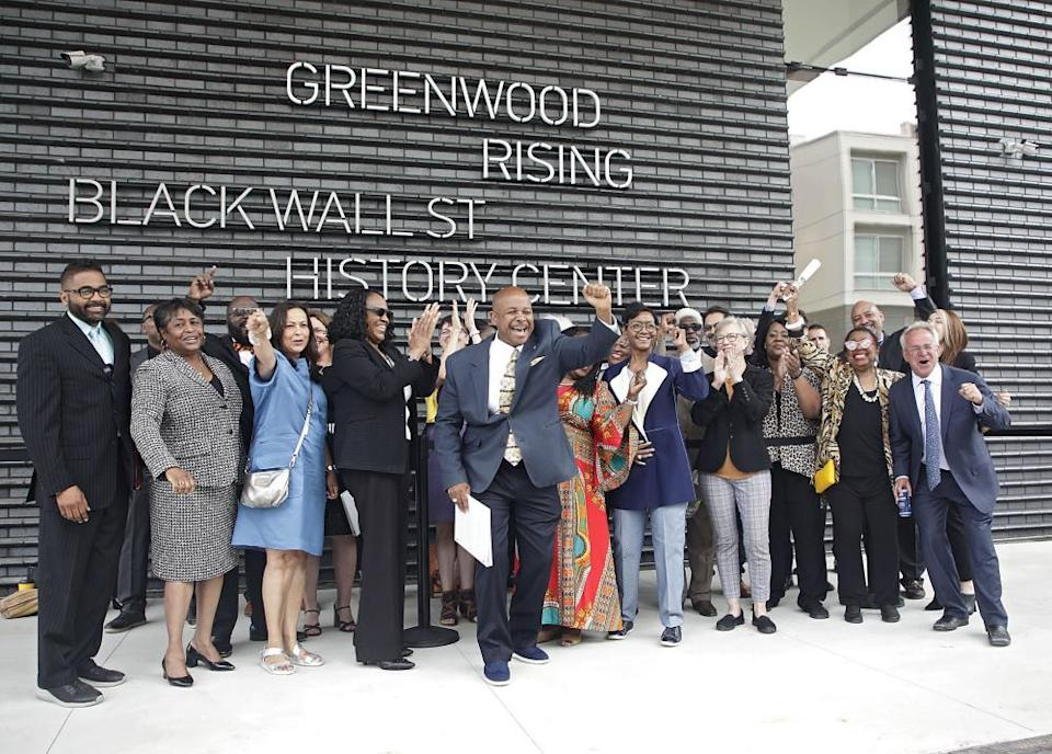 Members of the 1921 Tulsa Race Massacre Centennial Commission cheer while getting their picture taken in front of the Greenwood Rising Black Wall Street History Center on 2 June.