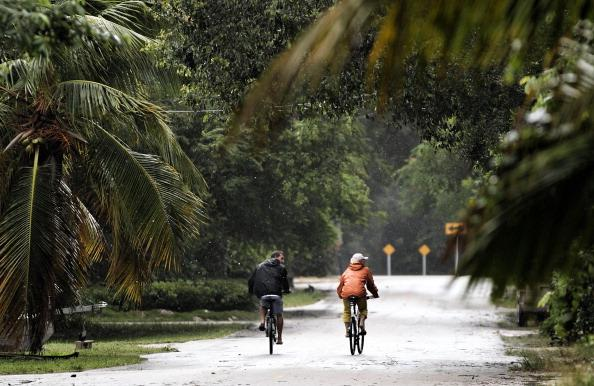 People ride bikes as as Tropical Storm Isaac begins to move ashore on August 26, 2012 in Marathon, Florida. According to reports, Isaac has become stronger as it moves toward the Florida Keys and forecasters say it could strengthen into a Category 2 storm. (Photo by Marc Serota/Getty Images)