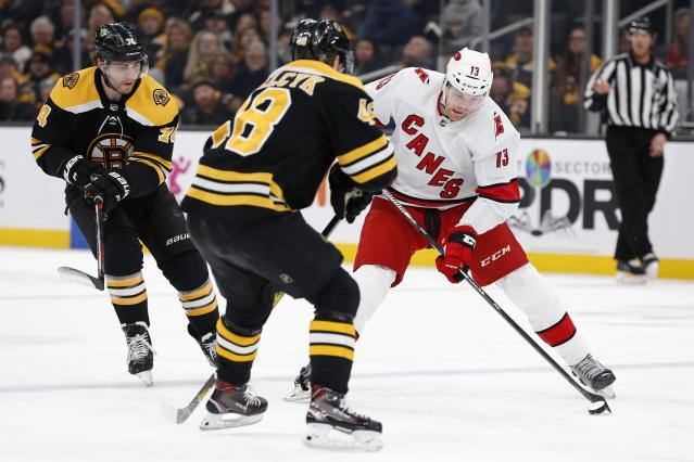 Boston Bruins' Matt Grzelcyk (48) defends against Carolina Hurricanes' Warren Foegele (13) during the first period of an NHL hockey game in Boston, Tuesday, Dec. 3, 2019. (AP Photo/Michael Dwyer)