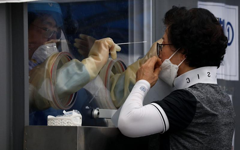 A medical worker takes samples from a woman at a temporary test facility in Seoul - Getty