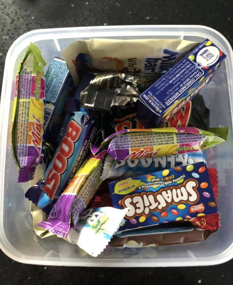 Photo shows a plastic container filled with chocolates.