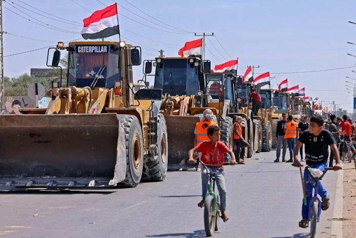Palestinian boys cycle past a convoy of bulldozers provided by Egypt arriving at the Palestinian side of the Rafah border crossing between Egypt and the Palestinian Gaza Strip enclave on June 4, 2021