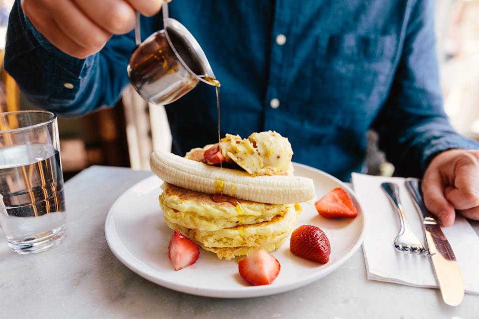 Man pouring maple syrup on pancakes with banana and strawberry.