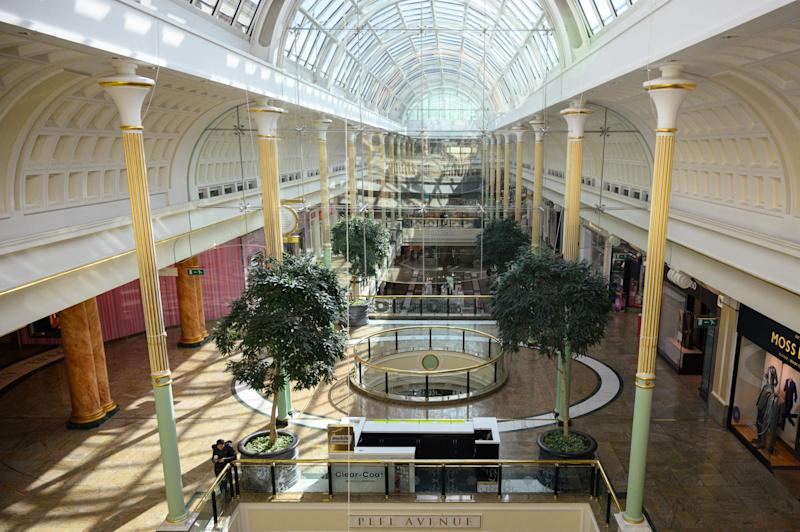 A shopper walks through a near-deserted Intu Trafford Centre shopping mall amidst the novel coronavirus COVID-19 pandemic, on the outskirts of Manchester, northern England on March 20, 2020. - The British prime minister urged people in his daily press conference on March 19 to be reasonable in their shopping as supermarkets emptied out of crucial items -- notably toilet roll -- across Britain. The government said it was temporarily relaxing elements of competition law to allow supermarkets to work together to maintain supplies. (Photo by Oli SCARFF / AFP) (Photo by OLI SCARFF/AFP via Getty Images)