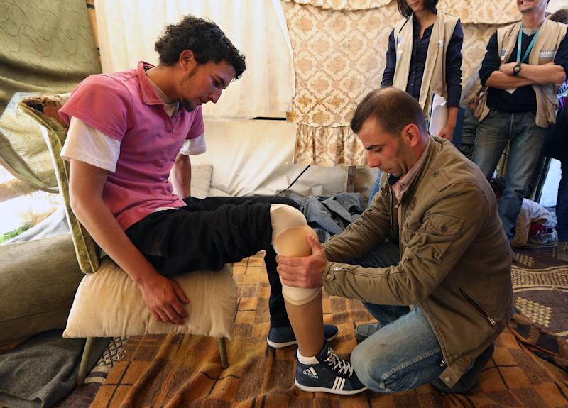 In this Thursday, March. 27, 2014 photo, Mustafa Ahmad, left, a 19-year-old who lost his leg in his hometown of Deir Hafer in Aleppo province in November 2011 when government warplanes bombed his neighborhood, is fitted with a prosthetic leg by a Lebanese prosthetic limb maker, right, at the Syrian refugee camp in Jib Janine, in the Bekaa valley, Lebanon. Syria's civil war, which entered its fourth year last month, has killed more than 150,000 people. An often overlooked figure is the number of wounded more than 500,000, according to the International Committee of the Red Cross. An untold number of those, there's no reliable estimate even, have suffered traumatic injuries that have left them physically handicapped. (AP Photo/Bilal Hussein)
