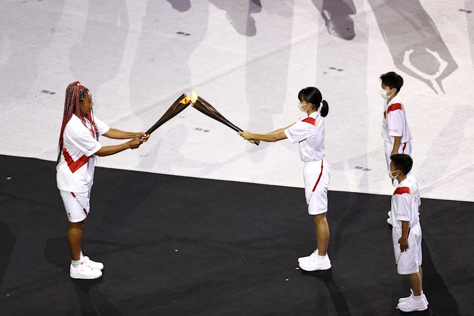 <p>TOKYO, JAPAN - JULY 23: Naomi Osaka of Team Japan is handed the Olympic torch during the Opening Ceremony of the Tokyo 2020 Olympic Games at Olympic Stadium on July 23, 2021 in Tokyo, Japan. (Photo by Maja Hitij/Getty Images)</p>