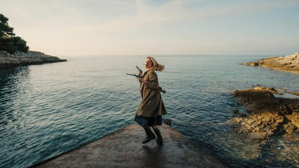 Mia Goth as Marsha in Mayday holding guns and standing before the water.