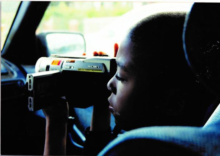 "A young boy in a car uses a video camera in the documentary ""17 Blocks."""