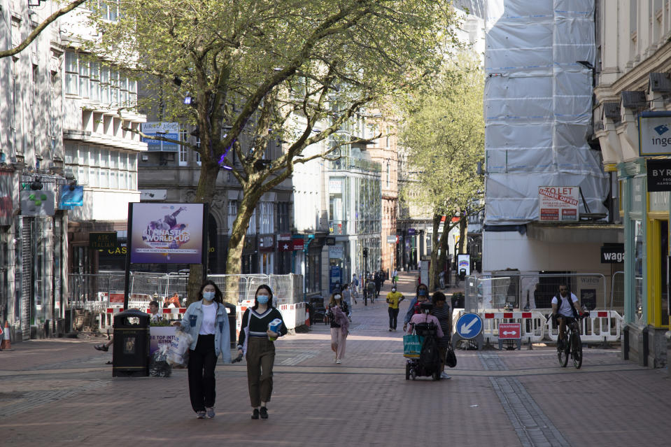 People wearing face masks in Birmingham city centre eerily quiet and deserted on New Street, one of the normally busy shopping areas, under lockdown due to Coronavirus on 24th April 2020 in Birmingham, England, United Kingdom. Coronavirus or Covid-19 is a new respiratory illness that has not previously been seen in humans. While much or Europe has been placed into lockdown, the UK government has extended stringent rules as part of their long term strategy, and in particular 'social distancing', which has left usually bustling areas like a ghost town. (photo by Mike Kemp/In PIctures via Getty Images)
